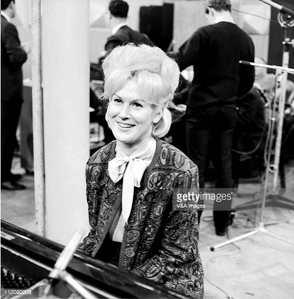 Dusty Springfield posed in recording studio sitting at piano 1962