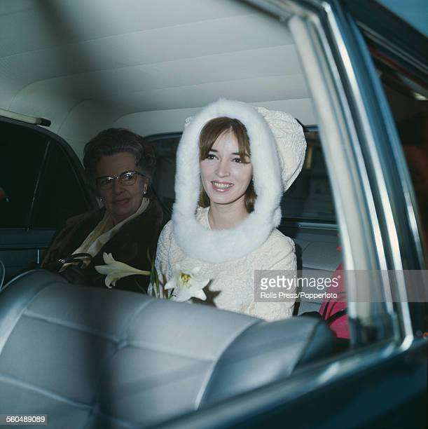 Dutch actress Talitha Pol pictured sitting in the back seat of a car wearing a white mini skirt with mink trim on the day of her wedding to John Paul...