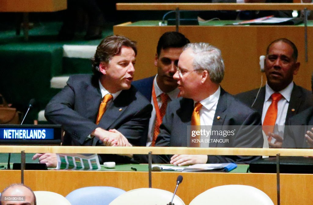 Dutch Ambassador to the United Nations Karel van Oosterom (R) shakes hands with Dutch Foreign Minister Bert Koenders after they announced an agreement of the Election of five non-permanent members of the Security Council at the United Nations in New York on June 28, 2016. / AFP / KENA