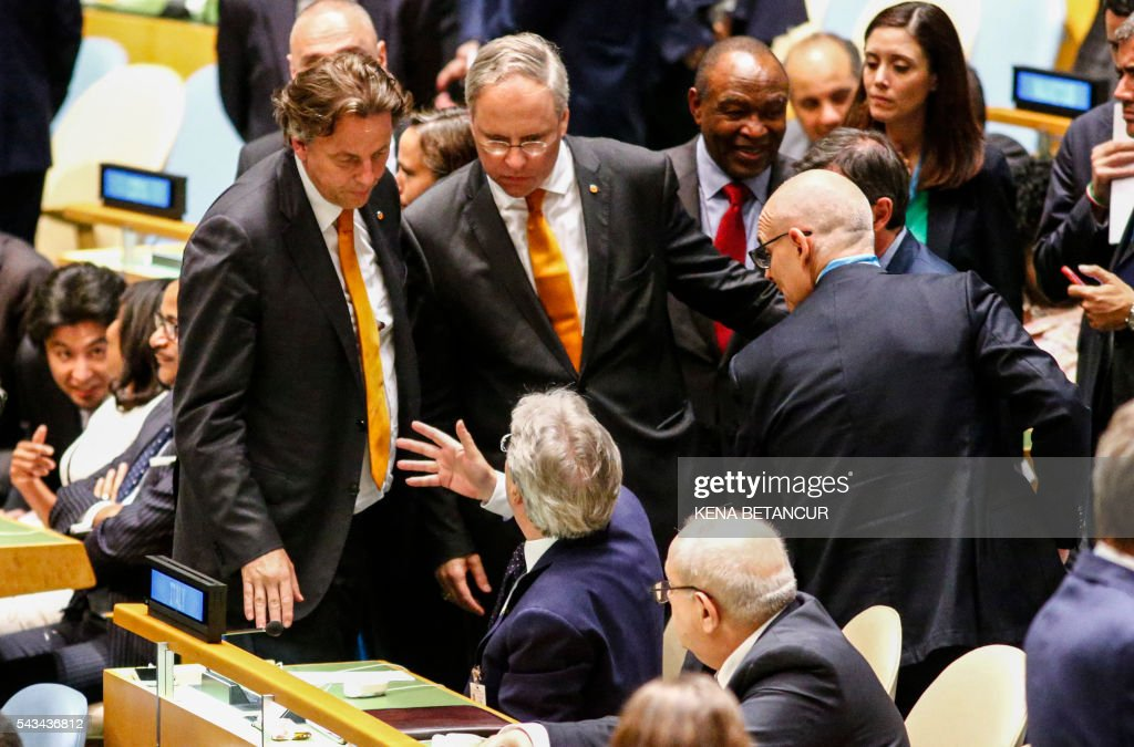 Dutch Ambassador to the United Nations Karel van Oosterom (C) Speaks to Italian Foreign Minister Paolo Gentiloni (Seated-C) while Dutch Foreign Minister Bert Koenders (L) and Italian Ambassador to the United Nations Sebastiano Cardi (R)listen after the fourth round of voting during the election of five non-permanent members of the Security Council at the United Nations in New York on June 28 2016. / AFP / KENA