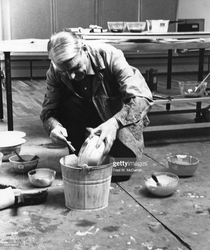 Dutch American artist Willem de Kooning (1904 - 1997) mixes paints in a metal bucket of the floor of his loft studio, New York, New York, March 23, 1962.