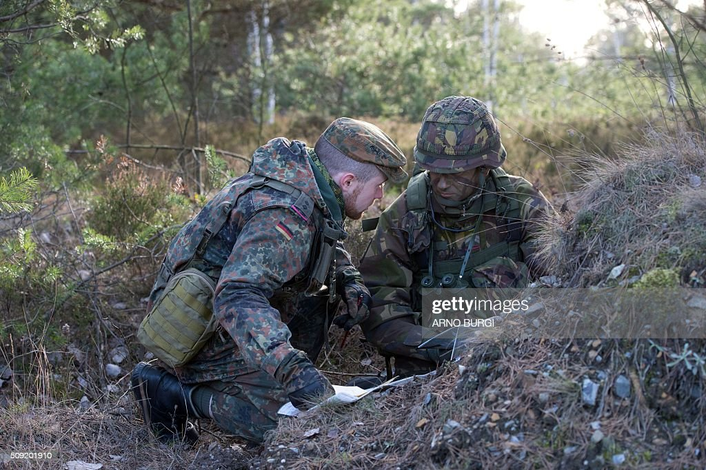 A Dutch (R) and a German soldier take part in a joint military exercise on February 9, 2016 at the Oberlausitz army training camp near Werdeck close to Weisswasser and the Polish border, eastern Germany. / AFP / dpa / Arno Burgi / Germany OUT