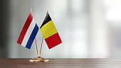Dutch and Belgian flag pair on desk over defocused background. Horizontal composition with copy space and selective focus.