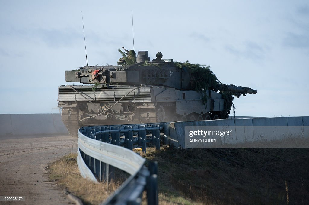 Dutch and German soldiers on a Leopard 2 tank take part in a joint military exercise on February 9, 2016 at the Oberlausitz army training camp near Werdeck close to Weisswasser and the Polish border, eastern Germany. / AFP / dpa / Arno Burgi / Germany OUT
