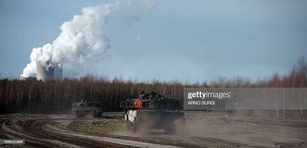 Dutch and German soldiers on Leopard 2 tanks take part in a joint military exercise on February 9, 2016 at the Oberlausitz army training camp near Werdeck close to Weisswasser and the Polish border, eastern Germany. / AFP / dpa / Arno Burgi / Germany OUT