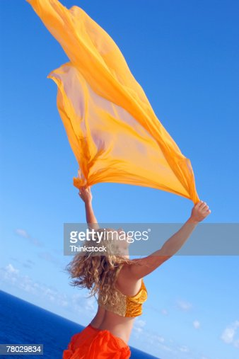 Dutch angle of a woman holding yellow sheer fabric high to blow in the wind