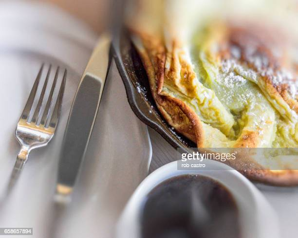 Dutch Baby Pancake on Skillet, Coffee, Plate, Knife and Fork