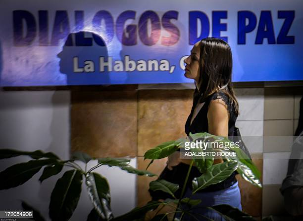 Dutch born member of FARCEP leftist guerrillas Tanja Nijmeijer passes in front of a poster announcing the peace talks between the FARC and the...