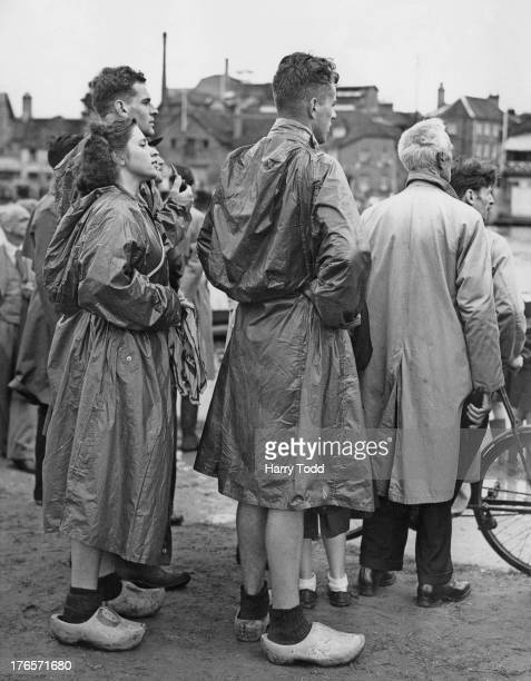 Dutch canoeists wearing clogs and raincoats watch their entrants return from the 10 000 metres Kayak Pairs event at the 1948 Summer Olympics...