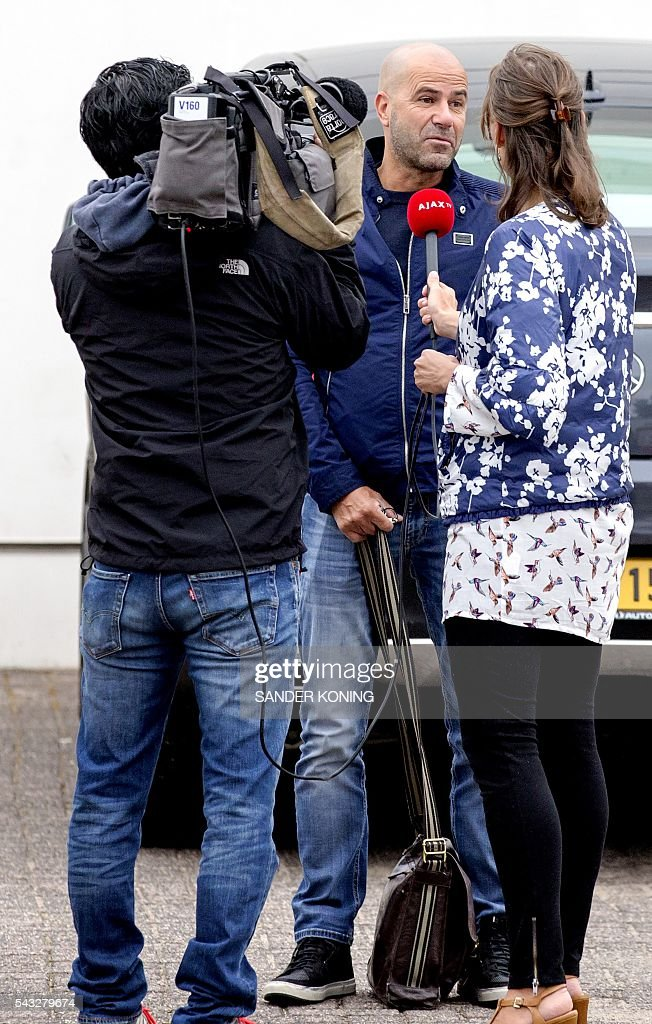 Dutch coach Peter Bosz of Ajax talks to journalists while arriving at the De Toekomst sport center in Amsterdam, on June 27, 2016, for the first training ahead of the Dutch Eredivisie football championship. Ajax have appointed Dutchman Peter Bosz as their new coach in place of Frank de Boer, the Amsterdam club confirmed on Tuesday. Bosz, 52, leaves his coaching position with Maccabi Tel Aviv to join the Dutch club on a three-year contract until June 2019. / AFP / ANP / Sander Koning / Netherlands OUT