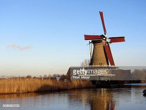 Dutch corn mill along canal : Stock Photo