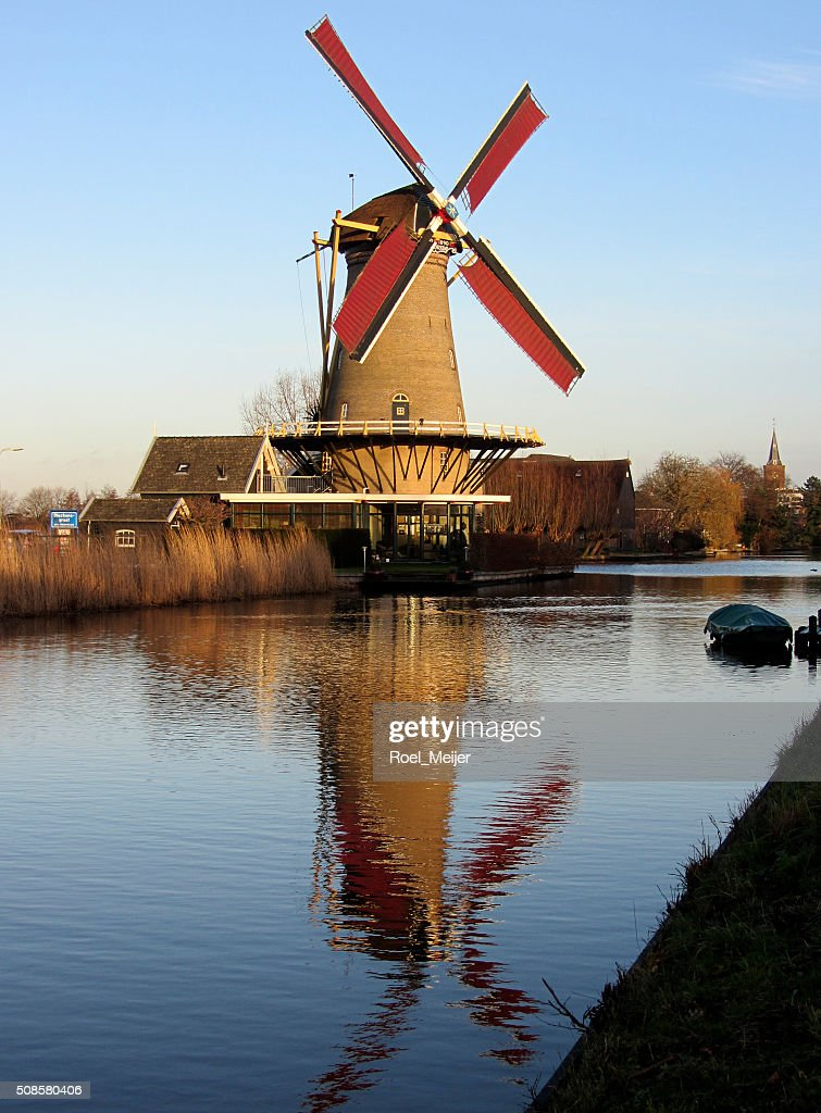 Dutch corn mill along canal, reflected in water : Stock Photo