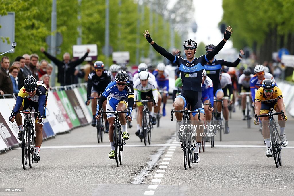 Dutch cyclist Jeff Vermeulen (C) raises his arms in victory as he crosses the finish line of the first stage of the Olympia Tour from Noordwijkerhout to Hoofddorp on May, 14 May 2013 in Hoofddorp. The event runs from 13 to 18 May 2013.