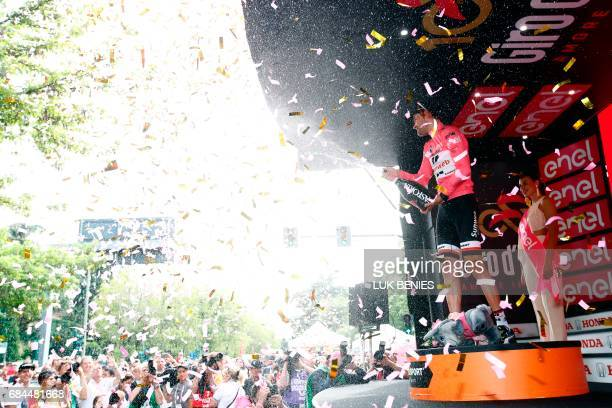 Dutch Cyclist Tom Dumoulin from Team Sunweb sprays champagne as he celebrates the pink jersey on the podium at the end of the 12th stage of the 100th...