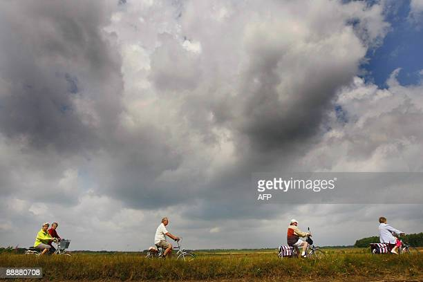Dutch cyclists pedal under rainy clouds nearby Aalden July 7 during a 4 day cycling tour in the Dutch region of Drenthe During this annual event...