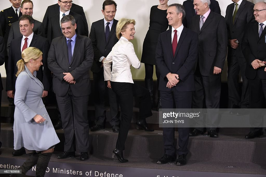 Dutch Defence minister Jeanine Hennis Plasschaert and her German counterpart <a gi-track='captionPersonalityLinkClicked' href=/galleries/search?phrase=Ursula+von+der+Leyen&family=editorial&specificpeople=4249207 ng-click='$event.stopPropagation()'>Ursula von der Leyen</a> run to pose for a family photo during a defence ministers meeting at the NATO headquarters in Brussels on February 5, 2015. NATO was set to agree a major boost to its defences including six bases in eastern Europe and a spearhead force of 5,000 troops in response to what it called Russian aggression in Ukraine.