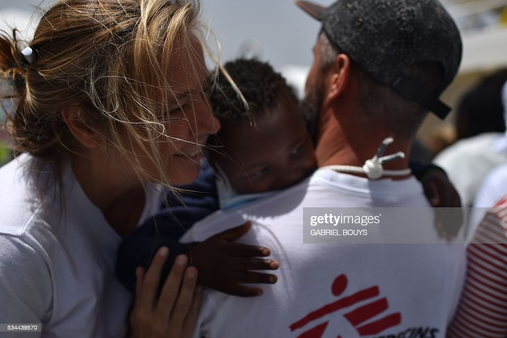 Dutch doctor Erna Rijnierse (L) of French NGO Doctors Without Borders (MSF) greets a child prior to disembark from rescue ship 'Aquarius' as more than 380 migrants arrive in the port of Cagliari, Sardinia, on May 26, 2016, two days after being rescued near the Libyan coasts. The Aquarius is a former North Atlantic fisheries protection ship now used by humanitarians SOS Mediterranee and Medecins Sans Frontieres (Doctors without Borders) which patrols to rescue migrants and refugees trying to reach Europe crossing the Mediterranean sea aboard rubber boats or old fishing boat. / AFP / GABRIEL