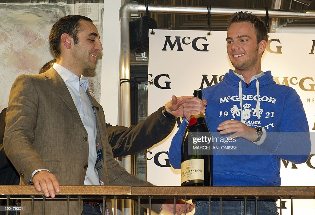 Dutch driver Giedo van der Garde (R) toasts with Caterham's team manager Cyril Abiteboul during a presentation event in Amsterdam, on February 1, 2013. Van der Garde will step up from reserve to be one of Caterham F1's main drivers this season.