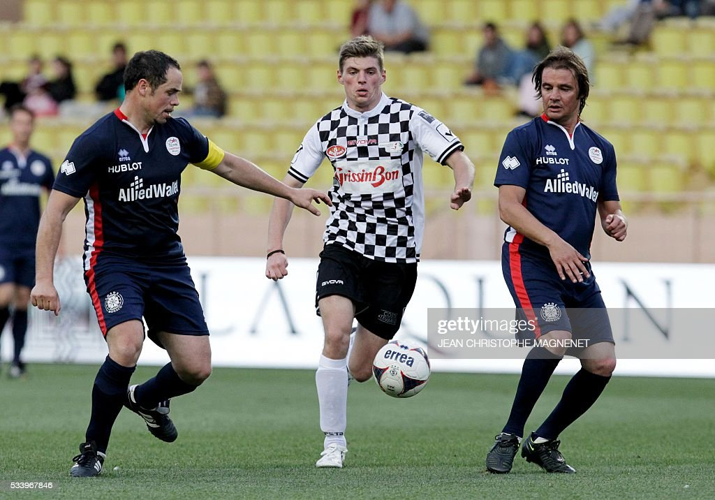 F1 Dutch driver Max Verstappen (C) vies for the ball during a charity football match between Prince Albert's Star Team and the F1 'Nazionale Piloti' drivers' team, for the benefit of the 'Association Mondiale des Amis de l'Enfance' (Protection of Children Association) on May 24, 2016 at the Louis II Stadium, in Monaco. / AFP / JEAN