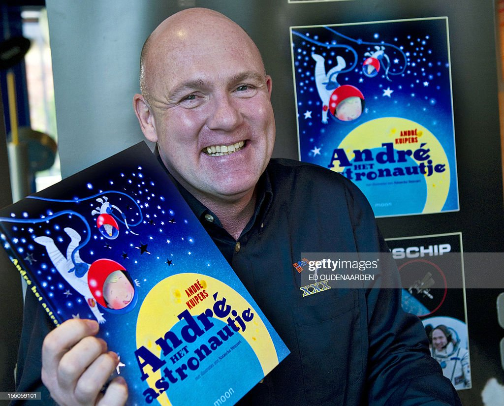 Dutch ESA astronaut Andre Kuipers poses with his book 'Andre het Astronautje' during its presentation at the Artis Zoo in Amsterdam on 31 October 2012. Kuipers presented three books about his life and his work after he stayed from last December until July in the International Space Station (ISS). netherlands out