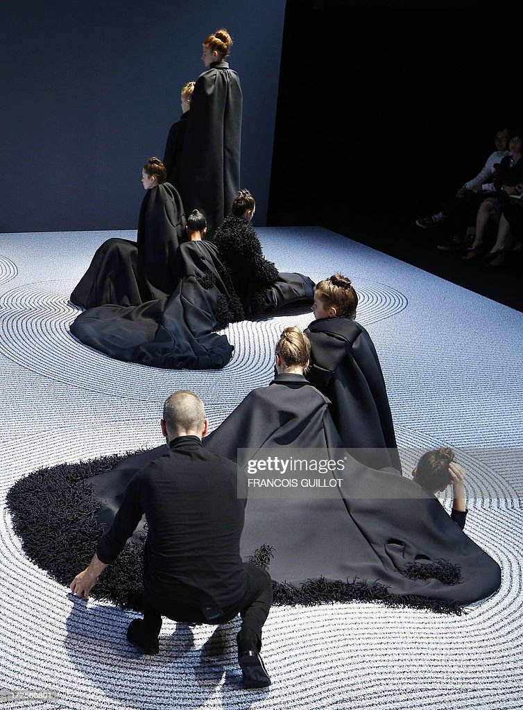 Dutch fashion designer Rolf Snoeren adjusts one of his creation on a model during the Viktor&Rolf Haute Couture Fall-Winter 2013/2014 collection show, on July 3, 2013 in Paris. AFP PHOTO/FRANCOIS GUILLOT
