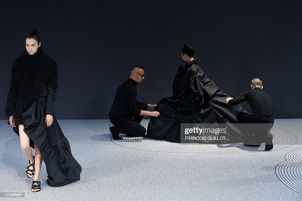 Dutch fashion designer Rolf Snoeren (R) and Viktor Horsting (C) adjust one of their creation on a model during the Viktor&Rolf Haute Couture Fall-Winter 2013/2014 collection show, on July 3, 2013 in Paris.