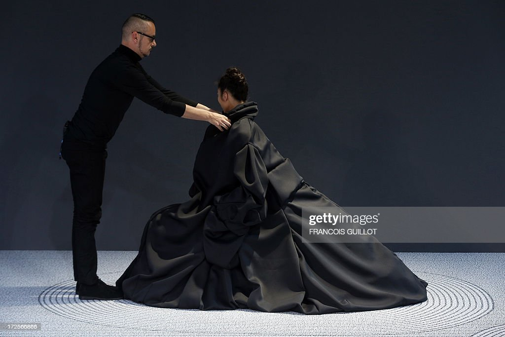 Dutch fashion designer Viktor Horsting adjusts one of his creation on a model during the Viktor&Rolf Haute Couture Fall-Winter 2013/2014 collection show, on July 3, 2013 in Paris.