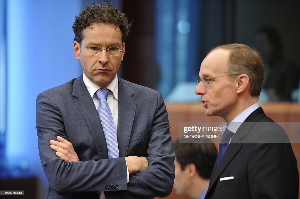 Dutch Finance Minister and Eurozone President Jeroen Dijsselbloem (L) talks with Luxembourg Finance Minister Luc Frieden prior to an Eurozone meeting on March 4, 2013 at the EU Headquarters in Brussels. Eurozone finance ministers meet today against a backdrop of a very weak economy and increased political uncertainty after inconclusive polls in Italy, the group's third largest economy and with the agenda the question of direct recapitalization of troubled banks and financial aid to Cyprus. AFP PHOTO / GEORGES GOBET