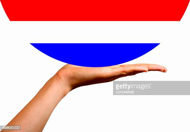 Dutch Flag in a hemisphere, on the palm of a hand.