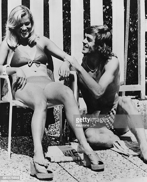 Dutch football player Johnny Rep relaxing with his wife Trudy in their bathing suits during a break between matches in the World Cup Hiltrup 1974