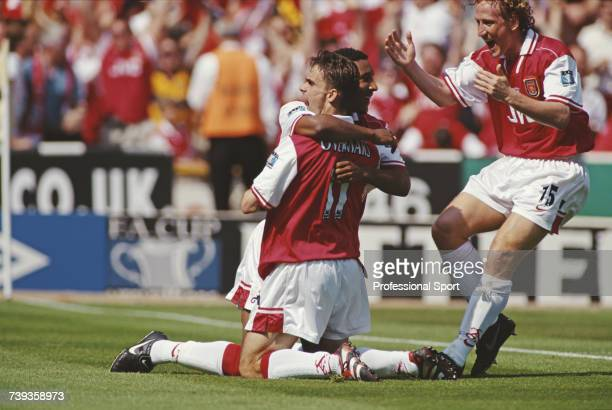 Dutch footballer and midfielder with Arsenal Marc Overmars is embraced by team mate Nicolas Anelka as Ray Parlour runs to join the celebration after...