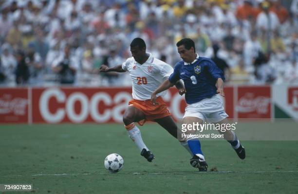 Dutch footballer Aron Winter closely marked by Brazilian midfielder Zinho makes a run with the ball during play in the 1994 FIFA World Cup...