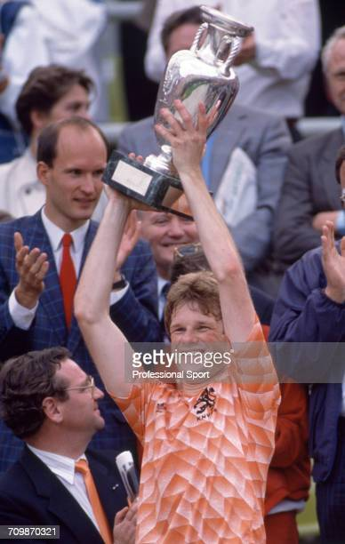 Dutch footballer Erwin Koeman raises the UEFA European Championship trophy in the air in celebration after Netherlands beat the Soviet Union 20 to...