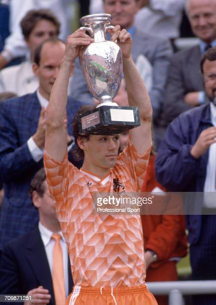 Dutch footballer Marco van Basten raises the UEFA European Championship trophy in the air in celebration after Netherlands beat the Soviet Union 20...