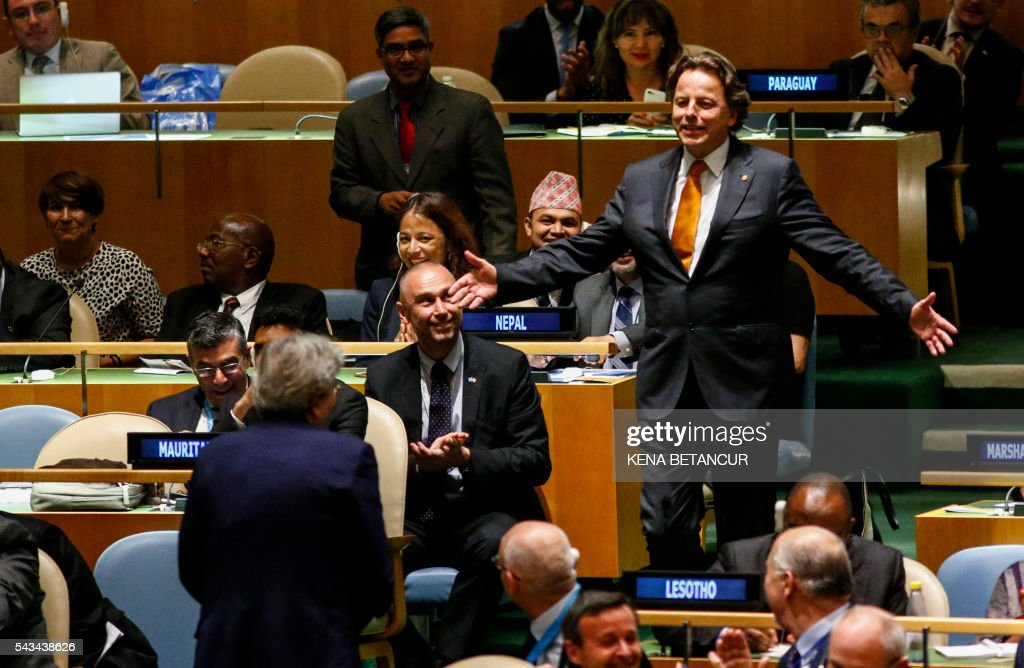 Dutch Foreign Minister Bert Koenders (R) gestures to Italian Foreign Minister Paolo Gentiloni (back to camera) after the results at the general assembly room after the fifth round during Election of five non-permanent members of the Security Council at the United Nations in New York on June 28, 2016. / AFP / KENA