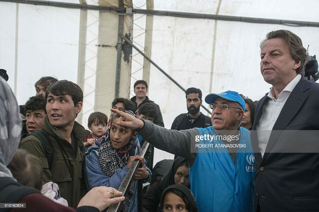 Dutch Foreign Minister Bert Koenders listens on as he meets with refugees in the transit and registration camp near Gevgelija on February 14, 2016. Dutch Foreign minister Bert Koenders spent an hour in a Vinojug recipient center near Gevgelija talking with migrants, children, UNICEF and Red Cross representatives, police and others members that are taking care of migrants that are heading to the EU from devastated homes in Syria, Afghanistan and Iraq. / AFP / Robert ATANASOVSKI