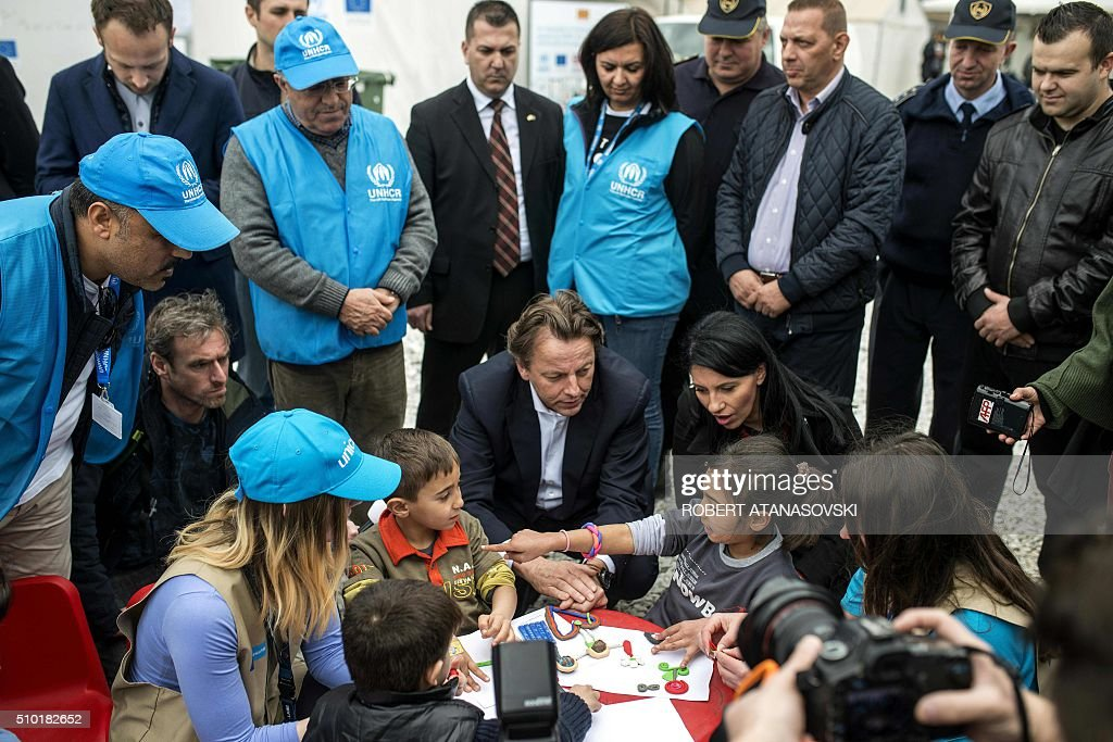 Dutch Foreign Minister Bert Koenders meets with young refugees in the transit and registration camp near Gevgelija on February 14, 2016. Dutch Foreign minister Bert Koenders spent an hour in a Vinojug recipient center near Gevgelija talking with migrants, children, UNICEF and Red Cross representatives, police and others members that are taking care of migrants that are heading to the EU from devastated homes in Syria, Afghanistan and Iraq. / AFP / Robert ATANASOVSKI