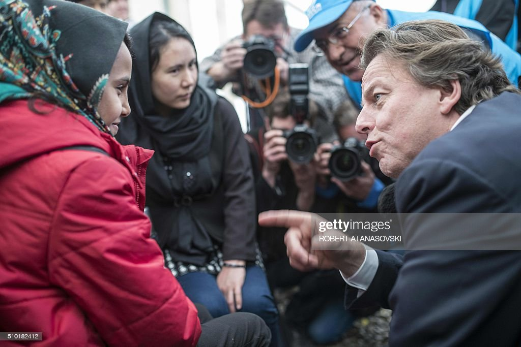 Dutch Foreign Minister Bert Koenders talks with young refugees in the transit and registration camp near Gevgelija, on February 14, 2016. Dutch Foreign minister Bert Koenders spent an hour in a Vinojug recipient center near Gevgelija talking with migrants, children, UNICEF and Red Cross representatives, police and others members that are taking care of migrants that are heading to the EU from devastated homes in Syria, Afghanistan and Iraq. / AFP / Robert ATANASOVSKI