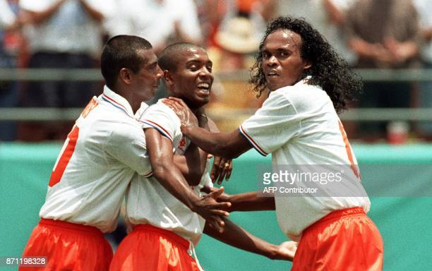 Dutch forward Bryan Roy is congratulated by teammates Gast Taument and Aron Winter 29 June 1994 in Orlando after Roy scored Holland's second goal...