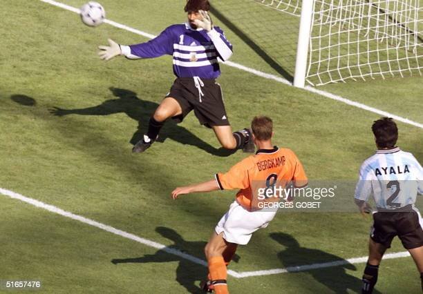 Dutch forward Dennis Bergkamp kicks the ball past Argentinian goalkeeper Carlos Roa to score th victory goal as Argentinian defender Roberto Ayala...
