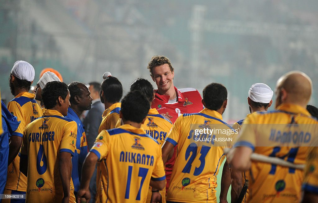 Dutch hockey goalkeeper Jaap Stockmann (C) shares a light moment with his Punjab Warriors teammates prior to the inaugural match of the Hockey India League (HIL) between Punjab Warriors and Delhi Waveriders in New Delhi on January 14, 2013.