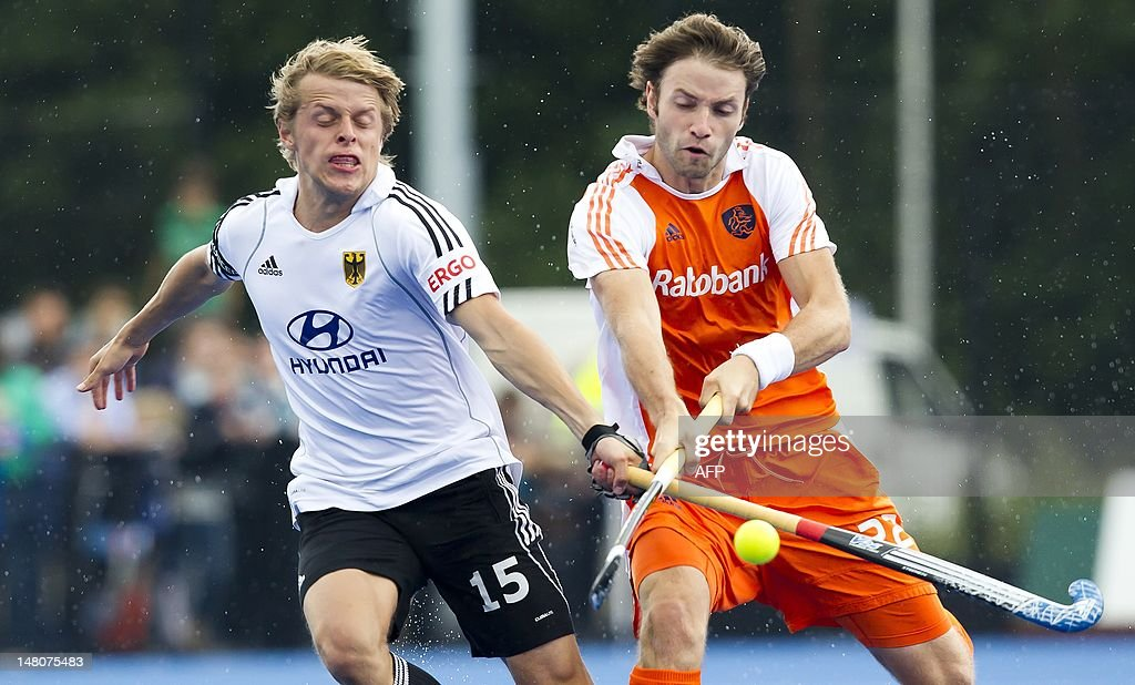 Dutch hockey player Rogier Hofman (R) in duel with German Benjamin Wess during a trial game between the Netherlands and Germany in preparation of the Olympic Games, in Utrecht on July 9, 2012. AFP PHOTO / ANP / KOEN SUYK netherlands out