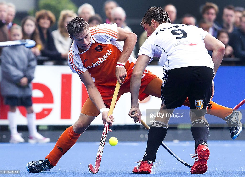 Dutch hockey player San de Wijn (L) vies with German Moritz Furste during a trial game between the Netherlands and Germany in preparation of the Olympic Games, in Utrecht on July 9, 2012. AFP PHOTO / ANP / KOEN SUYK netherlands out