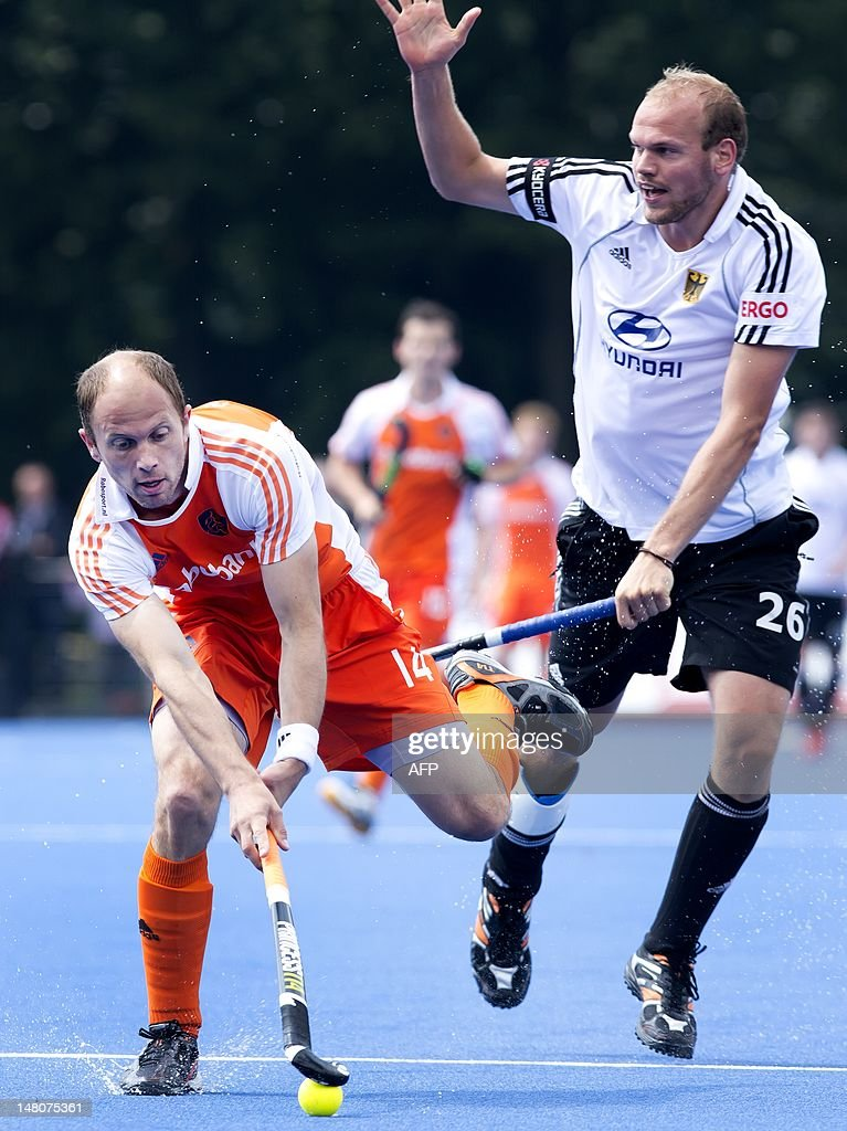 Dutch hockey player Teun de Nooijer (L) vies with German Thilo Stralkowski during a trial game between the Netherlands and Germany in preparation of the Olympic Games, in Utrecht on July 9, 2012. AFP PHOTO / ANP / KOEN SUYK netherlands out