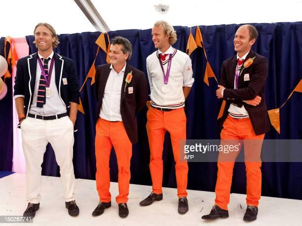 Dutch hockey players Roderick Weusthof Floris Evers and Teun de Nooijerhead pose with their coach Paul van Ass at The Hague on August 14 2012 during...