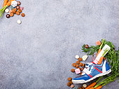 Dutch holiday Sinterklaas background with childrens shoe with carrots for Santa's horse, pepernoten and sweets with copy space. Top view.