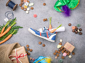 Dutch holiday Sinterklaas background with gifts, pepernoten, sweets and childrens shoe with carrots for Santa's horse. Flat lay with copy space. Top view.