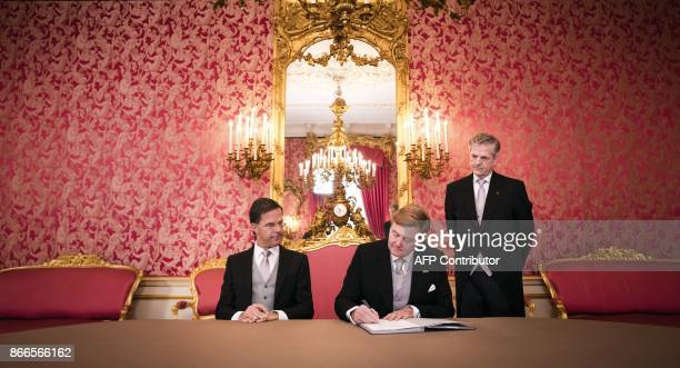 Dutch King WillemAlexander and Dutch Prime Minister Mark Rutte sign the Royal Decree at the Palace Noordeinde in The Hague on October 26 prior to the...