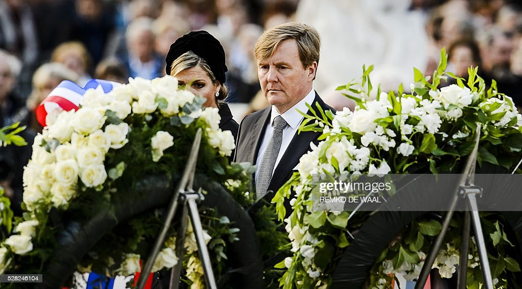 Dutch King Willem-Alexander (R) and Queen Maxima (L) lay a wreath during a National Remembrance ceremony at the National Monument on Dam Square in Amsterdam on May 4, 2016. The ceremony is held annually and commemorates all civilians and members of the armed forces of the Kingdom of the Netherlands who have died in wars or peacekeeping missions since the outbreak of World War II. / AFP / ANP / Remko de Waal / Netherlands OUT