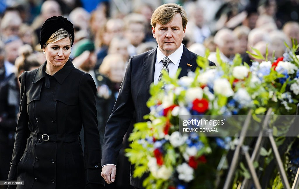 Dutch King Willem-Alexander (R) and Queen Maxima (L) walk past several wreaths during a National Remembrance ceremony at the National Monument on Dam Square in Amsterdam on May 4 2016. The ceremony is held annually and commemorates all civilians and members of the armed forces of the Kingdom of the Netherlands who have died in wars or peacekeeping missions since the outbreak of World War II. / AFP / ANP / Remko de Waal / Netherlands OUT